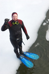 diver in wetsuit standing on river ice