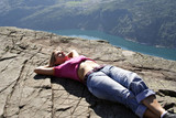 Girl lie on fjord cliff edge poster