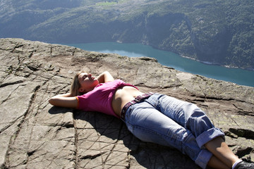 Girl lie on fjord cliff edge