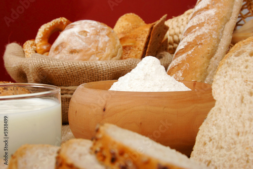 Assortment of baked breads with yoghurt and a bowl of flour