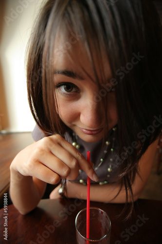 Anime-style girl drinking juice or cocktail through red straw.