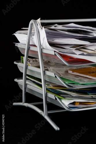 Messy in-basket with papers