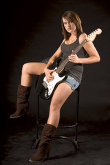 Teenaged girl sitting and playing electric guitar