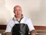 happy fishmonger in fish shop wearing black apron poster