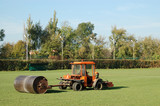 Tractor leveling soccer field using heavy metal lawn roller poster