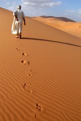 Lonely Berber man going ahead the Sahara Desert Morocco