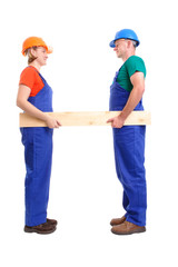 Female and male builders holding plank