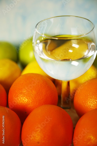 wine glass of water among oranges, lemons, apples