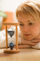 Young woman contemplating by an hourglass - shallow DOF