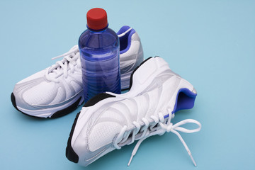 Sneakers with water bottle on blue background