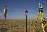 Total station, prism and plumb-bob in the field. poster