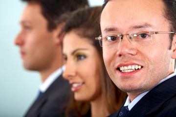 confident business man with glasses in an office smiling