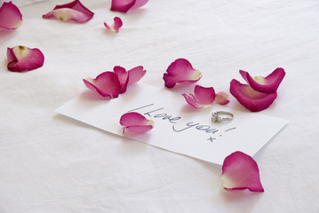 A handwritten love note and diamond engagement ring