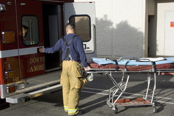 firefighter paramedic loading a gurney into the ambulance
