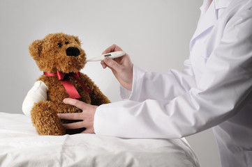 an injured teddy bear having a examination by a peadiatrician