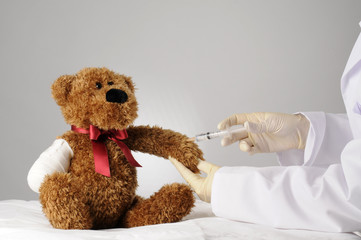 a teddy bear with an amputated claw getting an injection