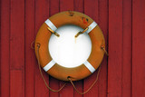 Orange lifebelt and lifeline on red wooden wall poster
