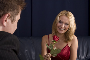 Man giving rose as gift to a beautiful blond girl who is smiling