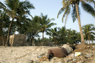 Homeless Indian lying on a heap of garbage. Goa. India