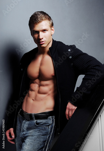 Sexy  man with beautiful body pose in the studio