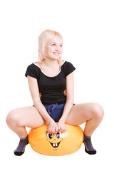 a smiling young woman going in for fitness sitting a big ball