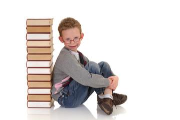 Young boy, prodigy next to enclyclopedia books.