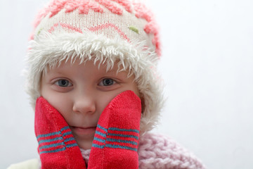 An image of a child in red mittens