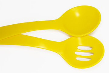Two yellow plastic spoons