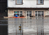 Canoeist paddles past flooded pub. River Ouse, York, UK. poster