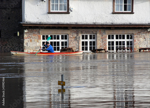 Canoeist paddles past flooded pub. River Ouse, York, UK.