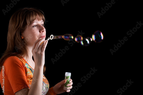 Girl looking to the bubbles isolated at the black background
