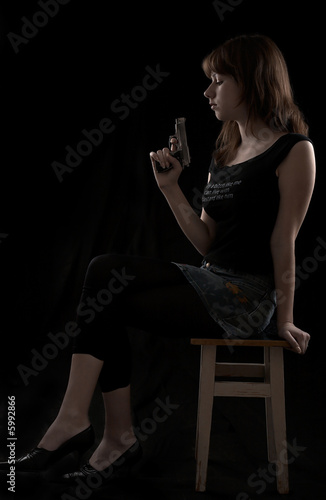 Young girl with gun isolated at the black background