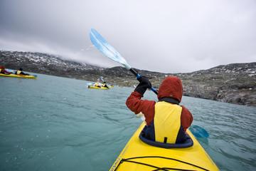 Young woman paddling in yellow kayak