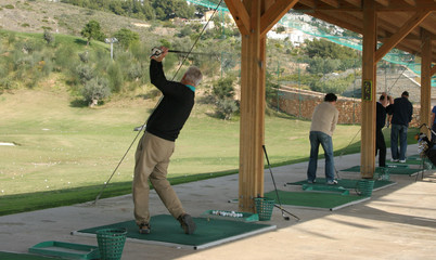 Golfers are practising on a driving range