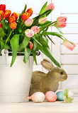 Pot of tulips with rabbit on the counter poster
