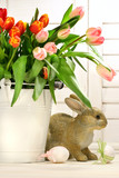 Rabbit hiding behind a white container of spring tulips poster
