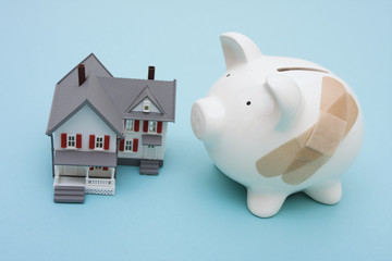 Piggy bank with adhesive bandage and house on blue background