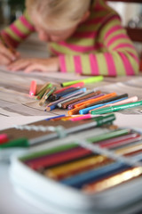 young child writting , painting and playing with colours