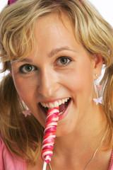 junge blonde hübsche Frau schleckt einen Lutscher