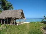case en paille sur la plage et lagon turquoise en fond poster
