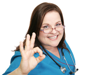 Pretty, enthusiastic nurse in scrubs giving the okay sign.
