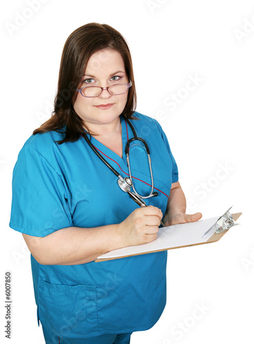Serious, plus-sized nurse taking notes in a medical chart.