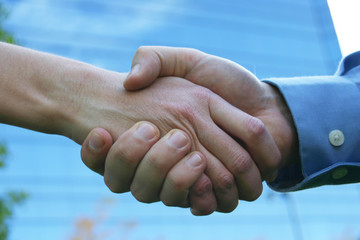 close up handshake with blue office building in background
