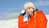 Young pretty girl playing snowball fight on flank of hill poster