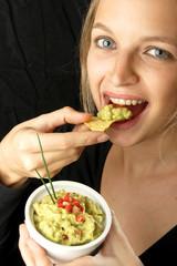 Frau isst chips mit guacamole