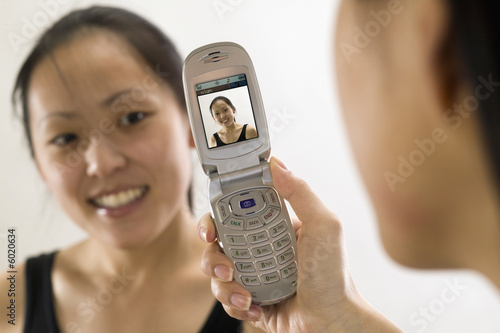 A young Asian girl posing for a camera phone photo