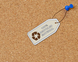 recycled material tag attached to corkboard with thumb tack poster