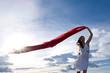 Frau winkt mit rotem Tuch vor blauem Himmel