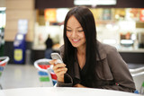 Fototapety Beautiful young woman smiling looking at mobile phone