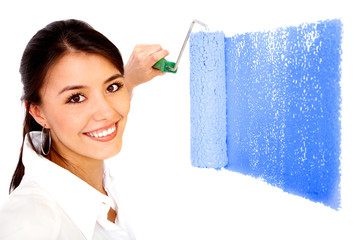beautiful woman painting a wall with a roller - isolated